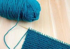 蓝色羊毛球与编织的在针 库存照片