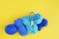 蓝色羊毛螺纹 螺纹、剪刀和一条被编织的围巾缠结  顶视图 手工制造的针线 库存图片