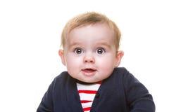 蓝色羊毛衫和红色镶边上面的愉快的微笑的女婴 免版税库存图片