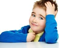 蓝色羊毛衫的快乐的男孩 免版税图库摄影