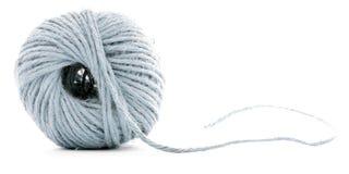 蓝色羊毛滚成线球,钩编编织物在白色背景隔绝的螺纹球 免版税库存图片