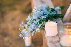 蓝色翠雀婚姻的新娘花束在一个老长木凳的 免版税库存照片