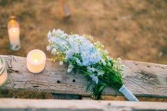 蓝色翠雀婚姻的新娘花束在一个老长木凳的 库存照片