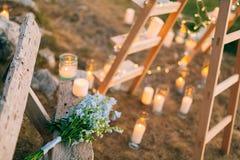 蓝色翠雀婚姻的新娘花束在一个老长木凳的 库存图片