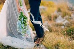 蓝色翠雀婚姻的新娘花束在增殖比的手上 库存照片