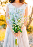 蓝色翠雀婚姻的新娘花束在增殖比的手上 库存图片