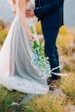 蓝色翠雀婚姻的新娘花束在增殖比的手上 免版税库存图片