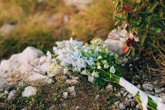 蓝色翠雀婚姻的新娘花束在岩石的 婚姻 库存图片