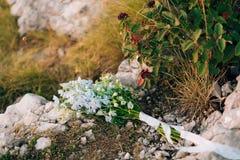 蓝色翠雀婚姻的新娘花束在岩石的 婚姻 图库摄影