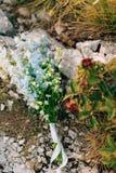 蓝色翠雀婚姻的新娘花束在岩石的 婚姻 免版税库存图片