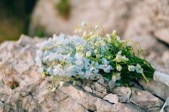 蓝色翠雀婚姻的新娘花束在岩石的 婚姻 库存照片