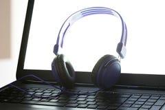 蓝色耳机基于有裁减路线的一手提电脑在您的文本的个人计算机屏幕和拷贝空间 库存图片