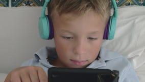 蓝色耳机的观看某事在片剂的一个男孩的特写镜头 股票视频