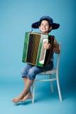 蓝色背景的一点手风琴球员 免版税库存图片