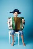 蓝色背景的一点手风琴球员 库存图片