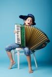 蓝色背景的一点手风琴球员 免版税库存照片
