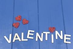 蓝色背景的华伦泰与红色心脏 库存图片