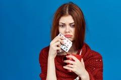 蓝色背景的少妇在围巾拿着药片的和杯子,流感,憔悴,病残,复制的空的空间 免版税库存照片