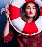 蓝色背景的美丽的女孩与一个气味强烈的红色圈子 海洋设计 免版税库存照片