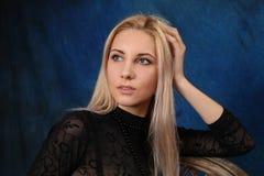 蓝色背景的美丽的金发碧眼的女人 库存照片