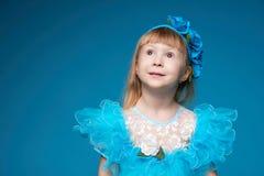 蓝色背景的逗人喜爱的小女孩 免版税库存图片