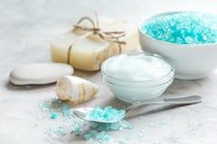蓝色腌制槽用食盐、润肤膏和壳温泉的在灰色桌背景 库存照片