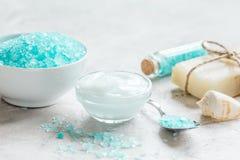 蓝色腌制槽用食盐、润肤膏和壳温泉的在灰色桌背景 免版税库存照片