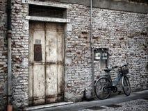 蓝色自行车对一个老被绘的白色砖墙和门 免版税库存图片
