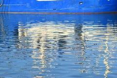 蓝色船和反射在水中 免版税图库摄影