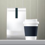 蓝色船锚咖啡杯和食物纸袋早餐集合 库存图片
