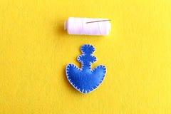蓝色船锚毛毡,白色螺纹,在黄色背景的一根针 孩子的基本的缝合的技术 指导 步骤 库存图片