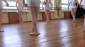 蓝色芭蕾衣服的女孩在第三个位置站立并且开始跳舞在磨损的芭蕾教室地板上的圈子  HD 股票视频