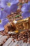 蓝色花、亚麻籽和油宏指令在木垂直 图库摄影