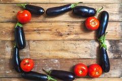 蓝色茄子和蕃茄框架在木板 库存照片