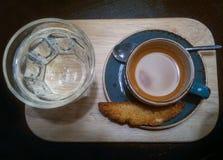 蓝色茶碟和咖啡杯在一个木盘子和一杯水 免版税库存图片