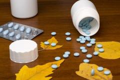 蓝色药片和医学瓶在木 免版税库存照片