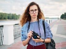 蓝色获得女衬衫和时髦的玻璃的年轻美丽的学生女孩与咖啡的乐趣摆在河pi的和照片照相机 免版税库存照片