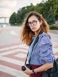 蓝色获得女衬衫和时髦的玻璃的年轻美丽的学生女孩与咖啡的乐趣摆在河pi的和照片照相机 图库摄影