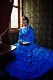 蓝色葡萄酒礼服的少妇读在r小轿车的书  免版税库存图片