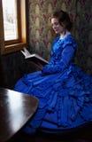蓝色葡萄酒礼服的少妇读在r小轿车的书  库存图片