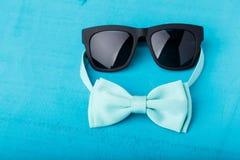 蓝色蝶形领结和太阳镜 免版税库存照片