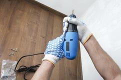 蓝色螺丝刀在反对木室内地板和白色墙壁的男性手上 改造工程的概念 免版税库存照片