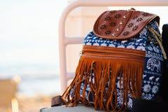 蓝色行家背包正面图有大而无用的东西样式和皮革边缘的在海滩的椅子 库存图片