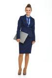 蓝色衣服待办卷宗的愉快的女实业家在胳膊下 免版税库存图片
