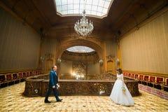蓝色衣服的典雅的新郎和去俏丽的新娘在老冰屑玻璃天花板前面的葡萄酒房子互相遇见  图库摄影