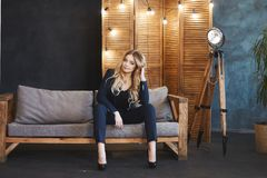 蓝色衣服的年轻白肤金发的企业夫人坐在现代内部的木沙发 免版税图库摄影