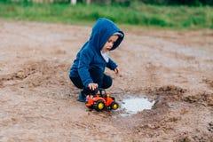 蓝色衣服的男孩使用与在土的一辆玩具汽车 免版税库存照片