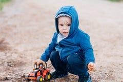 蓝色衣服的男孩使用与在土的一辆玩具汽车 免版税图库摄影
