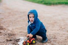 蓝色衣服的男孩使用与在土的一辆玩具汽车 免版税库存图片