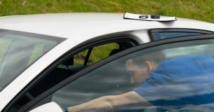 蓝色衣服的维护工作者,被打开门和检查汽车 免版税库存图片